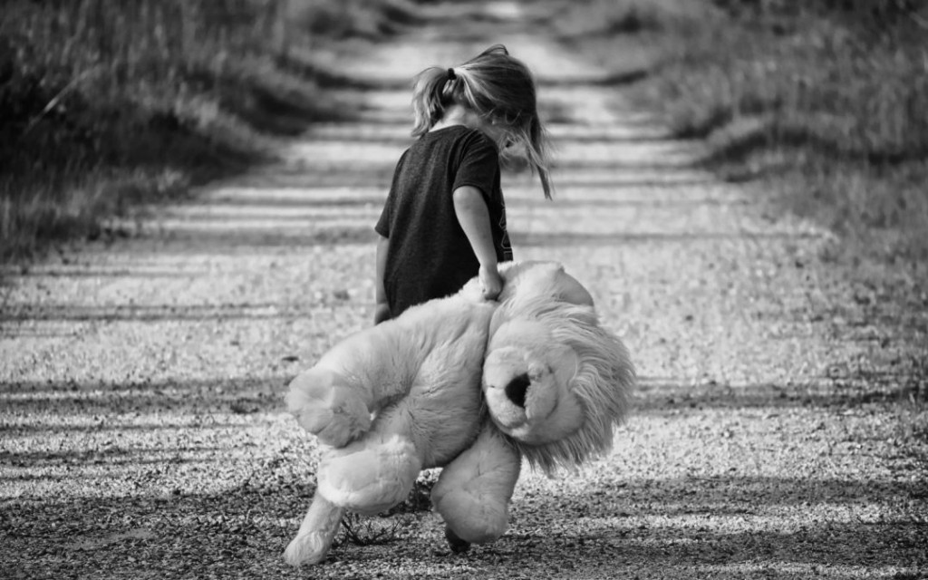 black-and-white-image-of-girl-carrying-teddy-bear-1080x675